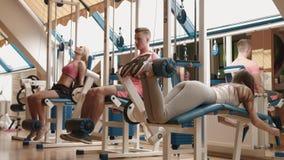 Deporte y concepto sano del estilo de vida Tres personas jovenes en ropas de deportes se están resolviendo en el gimnasio Waming  metrajes
