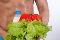 Deporte y dieta Hombre atractivo con el cuerpo muscular Individuo y verduras atléticos imagenes de archivo