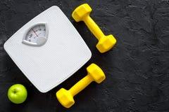 Deporte y dieta para el peso perdidoso Báscula de baño, manzana y pesa de gimnasia en copyspace negro de la opinión superior del  Fotos de archivo libres de regalías