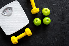 Deporte y dieta para el peso perdidoso Báscula de baño, manzana y pesa de gimnasia en copyspace negro de la opinión superior del  Fotografía de archivo