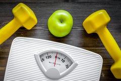 Deporte y dieta para el peso perdidoso Báscula de baño, manzana y pesa de gimnasia en la opinión superior del fondo de madera Imagen de archivo