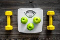 Deporte y dieta para el peso perdidoso Báscula de baño, manzana y pesa de gimnasia en la opinión superior del fondo de madera Imagen de archivo libre de regalías