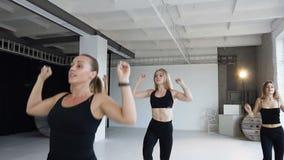 Deporte y forma de vida sana El grupo de muchachas atléticas en monos negros realiza el paso del calentamiento aerobio en estudio almacen de video