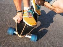 Deportes de alta velocidad de la calle: Un individuo en zapatillas de deporte amarillas está rodando en un longboard a lo largo d Fotos de archivo libres de regalías