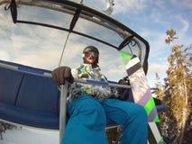 Deportes de invierno - snowboarder que usa el teleférico Imagen de archivo libre de regalías