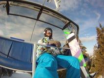 Deportes de invierno - snowboarder que usa el teleférico Fotografía de archivo libre de regalías