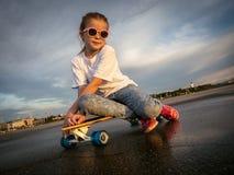 Deportes de la calle: Jolly Girl en gafas de sol se sentó para relajarse en el longboard después de un paseo en el parque para pa fotografía de archivo libre de regalías