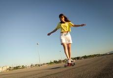 Deportes de la calle: Una muchacha en una camiseta amarilla brillante está rodando en un longboard en el asfalto del ` s de la ci imagen de archivo libre de regalías