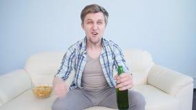 Deportes de observación del hombre joven en la TV y el equipo de apoyo en casa almacen de metraje de vídeo