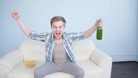 Deportes de observación del hombre joven en la TV y el equipo de apoyo en casa almacen de video