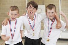Deportes masculinos Team In Gym With Medals de la escuela foto de archivo