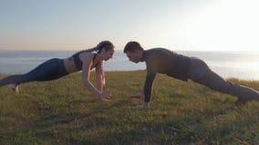 Deportes que entrenan en el aire abierto, par atlético que hace ejercicio durante puesta del sol en una montaña contra un paisaje metrajes