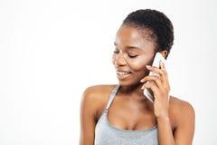 Deportista afroamericana joven preciosa linda que habla en el teléfono móvil Foto de archivo libre de regalías