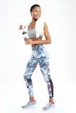 Deportista afroamericana sonriente que coloca y que sostiene la botella de agua Fotos de archivo libres de regalías