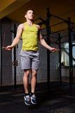 Deportista atlético joven en el sportwear que trabaja con la cuerda de salto en gimnasio apto de la cruz contra la pared de ladri Fotos de archivo libres de regalías