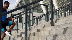 Deportista atlético que funciona con para arriba las escaleras, entrenando en el estadio, forma de vida sana imagen de archivo