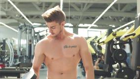 Deportista atractivo que se resuelve con pesas de gimnasia en gimnasio almacen de metraje de vídeo