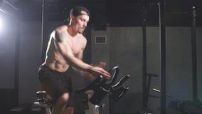 Deportista de pecho desnudo contratado a un simulador de la bicicleta en el gimnasio metrajes