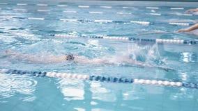 Deportista de sexo masculino del alto ángulo que flota en estilo del arrastre por las pistas en el campeonato de la piscina almacen de video