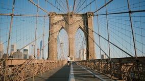 Deportista de sexo masculino que corre a lo largo del puente de Brooklyn, Nueva York en un día de verano soleado Tiro hermoso 4K  almacen de video
