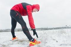 Deportista durante la sesión de formación al aire libre del invierno en el fondo nevoso del campo Foto de archivo libre de regalías