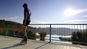 Deportista en pcteres de ruedas en el verano En línea patinando en el camino del lago Ejercicio contra al sol almacen de metraje de vídeo