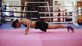 Deportista en sujetador y pantalones cortos que hacen pectorales en sus puños en la estera del ejercicio dentro del ring de boxeo almacen de metraje de vídeo