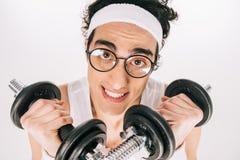 Deportista flaco joven en las lentes que llevan a cabo pesas de gimnasia imagen de archivo