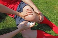 Deportista herido que es ayudado por el terapeuta Fotografía de archivo