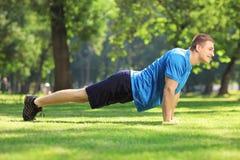 Deportista hermoso joven que ejercita en un parque Fotos de archivo