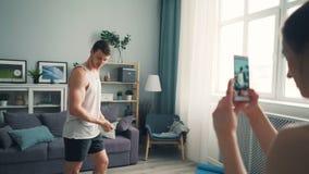 Deportista hermoso que presenta para la cámara del smartphone mientras que la muchacha está registrando el vídeo almacen de video
