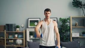 Deportista hermoso que se resuelve con las pesas de gimnasia que aumentan los brazos que practican en casa almacen de metraje de vídeo