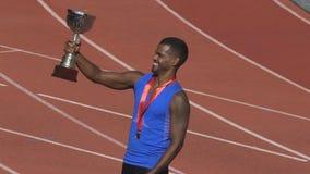 Deportista hispánico con la medalla de oro en el pecho que sostiene la taza, realizando su victoria almacen de metraje de vídeo