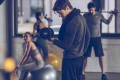 Deportista joven atlético que ejercita con pesa de gimnasia en el gimnasio Fotos de archivo