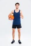 Deportista joven feliz que sostiene la bola del baloncesto y que muestra los pulgares para arriba Fotografía de archivo