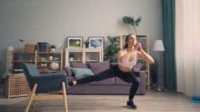 Deportista joven hermosa que hace posiciones en cuclillas en casa usando cuerpo del entrenamiento de la butaca almacen de video