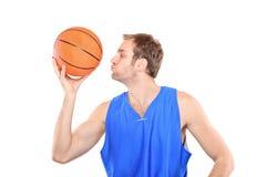 Deportista joven que besa un baloncesto Imágenes de archivo libres de regalías