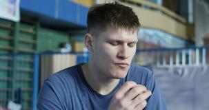 Deportista joven que come en gimnasio almacen de metraje de vídeo