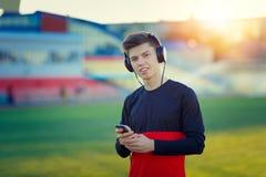 Deportista joven que descansa y que escucha la música Fotos de archivo libres de regalías