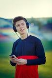 Deportista joven que descansa y que escucha la música Imagenes de archivo