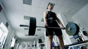 Deportista joven que hace ejercicio del deadlift con un barbell en un gimnasio metrajes