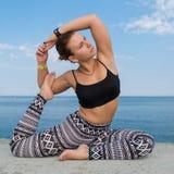 Deportista joven que hace ejercicios contra el mar foto de archivo