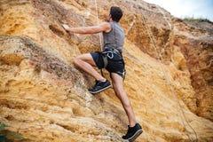 Deportista joven que sube para arriba un acantilado de la roca Imagen de archivo