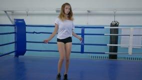 Deportista muscular en pantalones cortos cortos usando la cuerda de salto para permanecer ajuste en el ring de boxeo metrajes