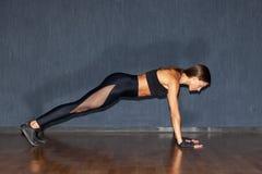 Deportista muscular hispánica en ropa de deportes negra Fotos de archivo