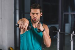 deportista muscular que ejercita con pesas de gimnasia fotos de archivo libres de regalías