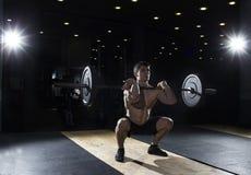 Deportista muscular que hace el ejercicio agazapado delantero en el gimnasio Fotos de archivo
