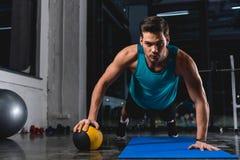 deportista muscular que hace pectorales con la bola de medicina en la estera de la yoga fotografía de archivo