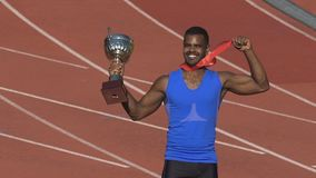 Deportista muscular que muestra su medalla y taza para la victoria a las fans en soportes metrajes