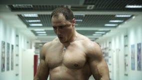 Deportista muscular que presenta en el gimnasio metrajes
